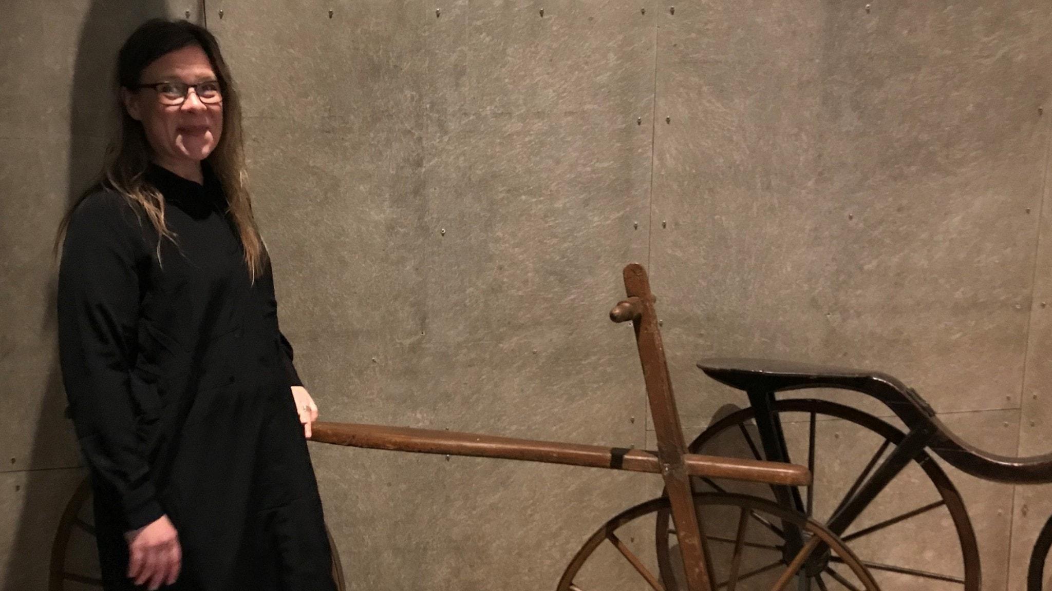 Karin Carlsson med en riktigt gammaldags cykel, i trä