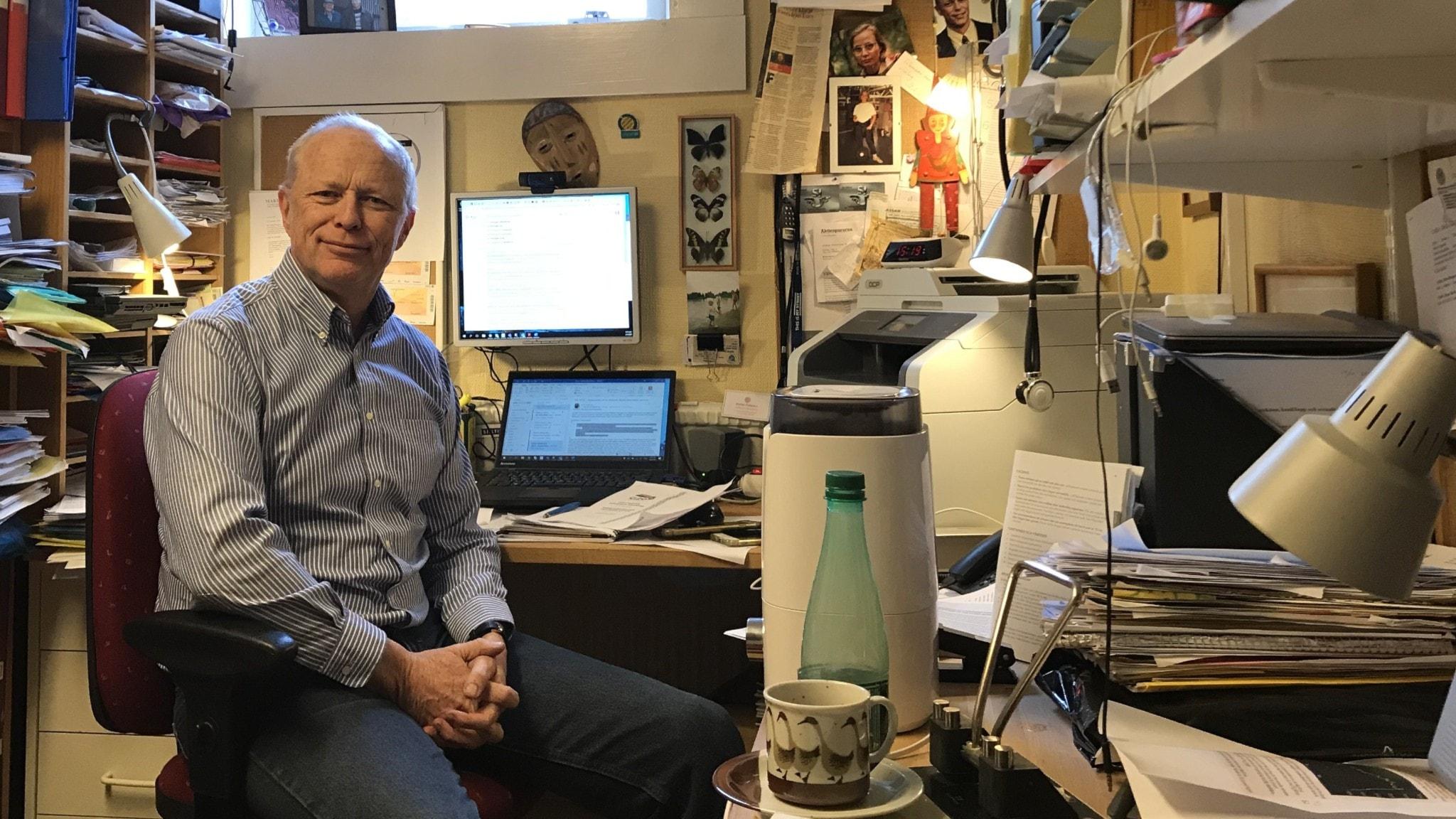 Stefan Swartling Peterson i ett litet smalt kontorsrum fullt med papper. Bakom honom ett källarfönster.