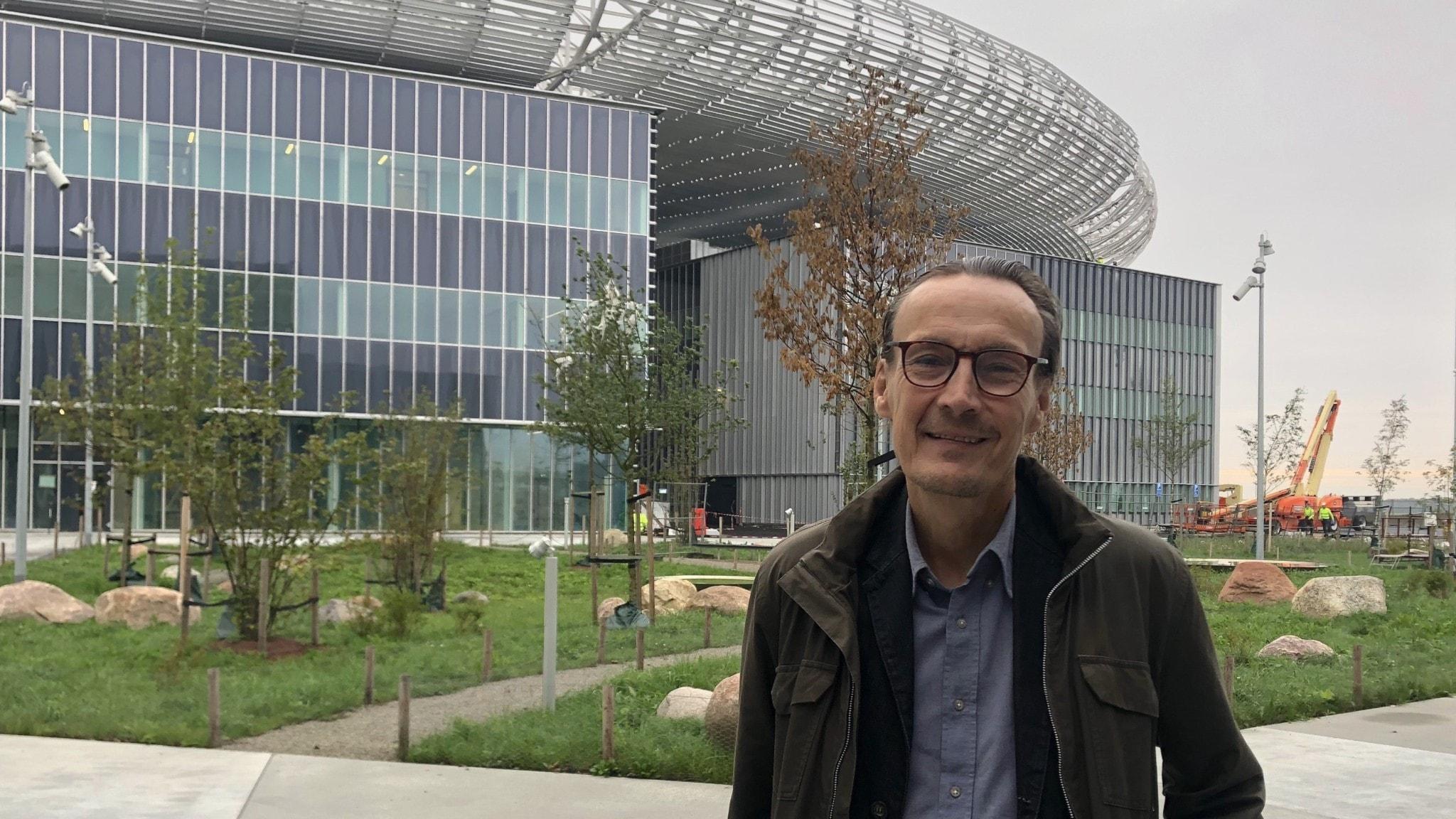 En man står vänd mot kameran och ler. Bakom honom syns en modern byggnad i glas och metall, samt några byggmaskiner.