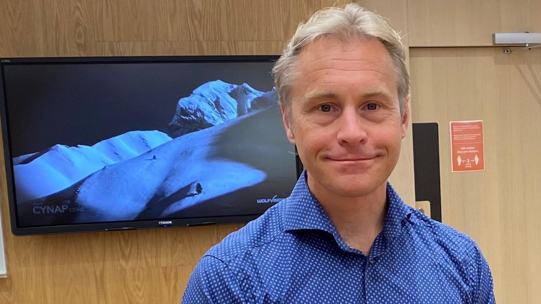 Per Carlbring i blå skjorta, framför en skärm på väggen.