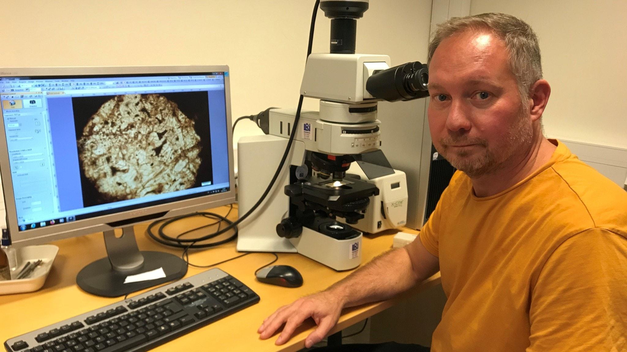 Magnus Ivarsson med vad som kanske är fossil från världens äldsta svamp, i mikroskopet.