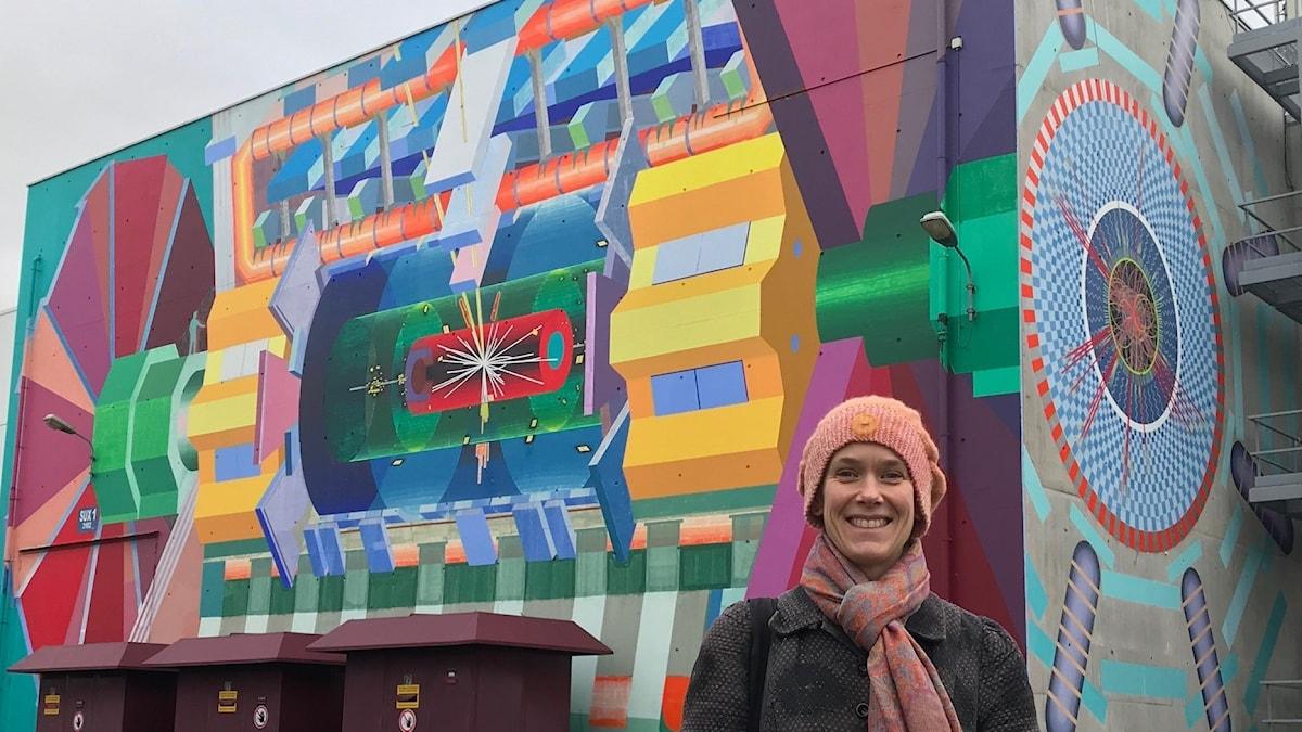 Sara Strandberg framför vägg på Cern-området där en konstnär har målat Atlasdetektorns inre i många färger.
