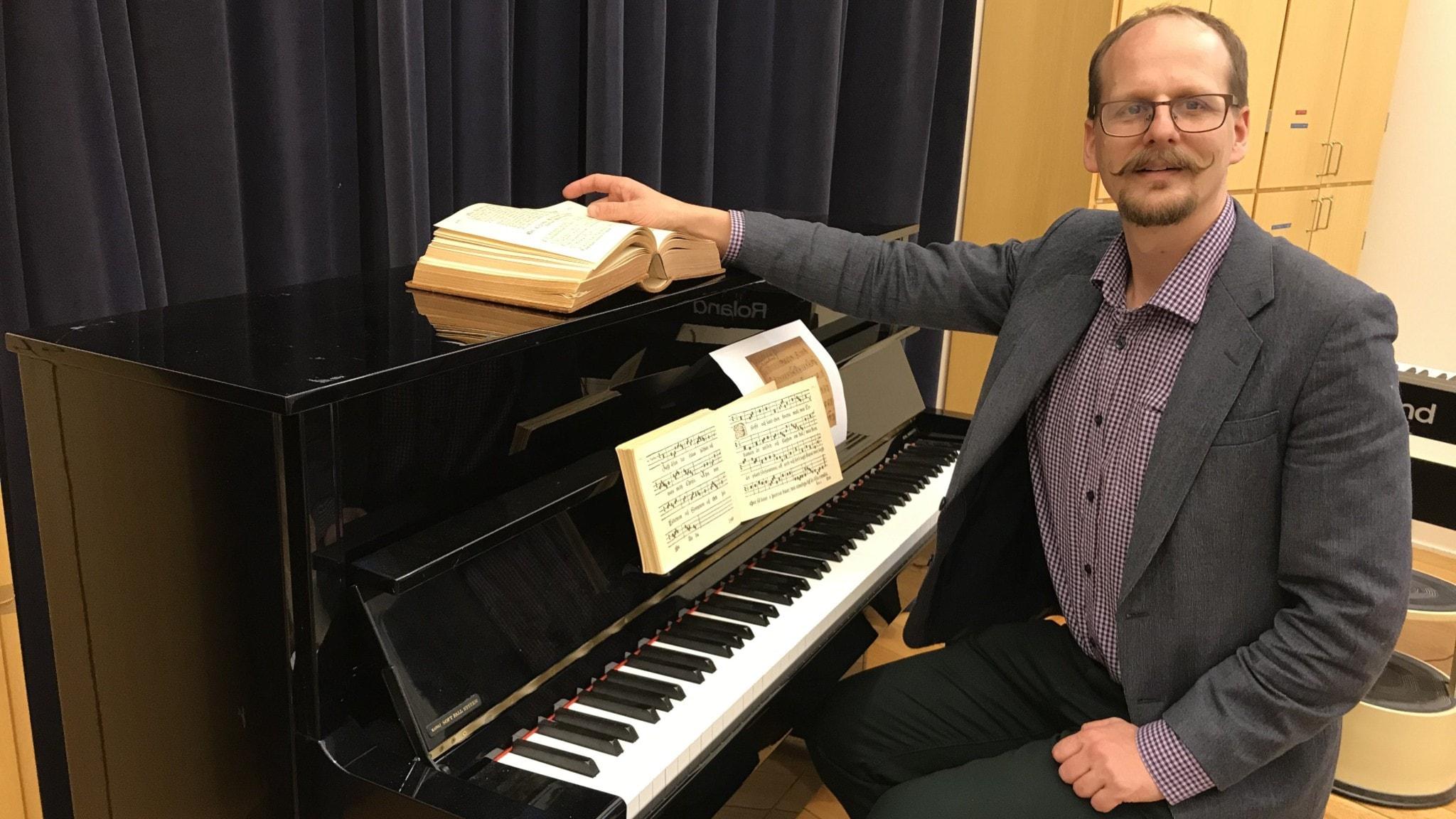 Mattias Lundberg vid ett svart piano med gamla notböcker på.