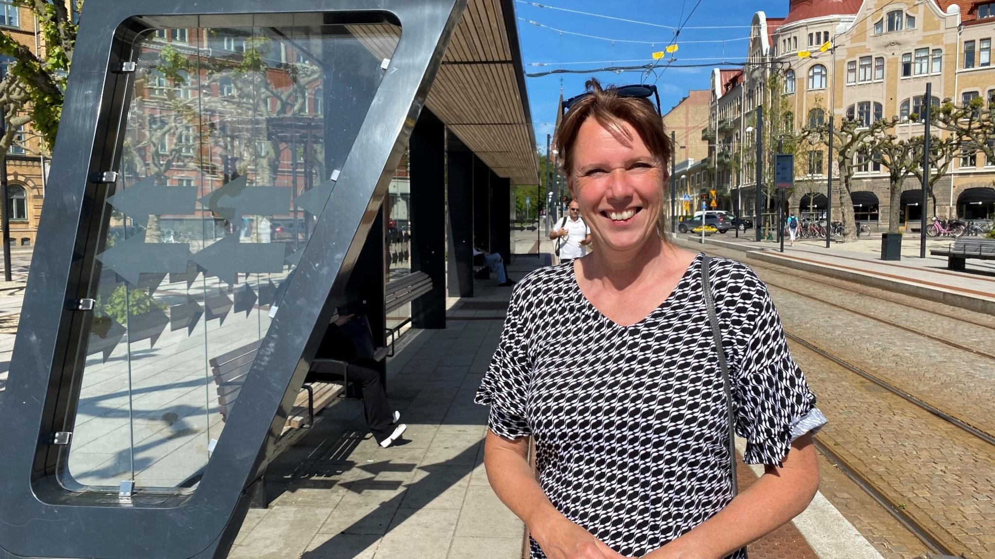 Lena Winslott Hiselius står vid spårvagnshållplats.