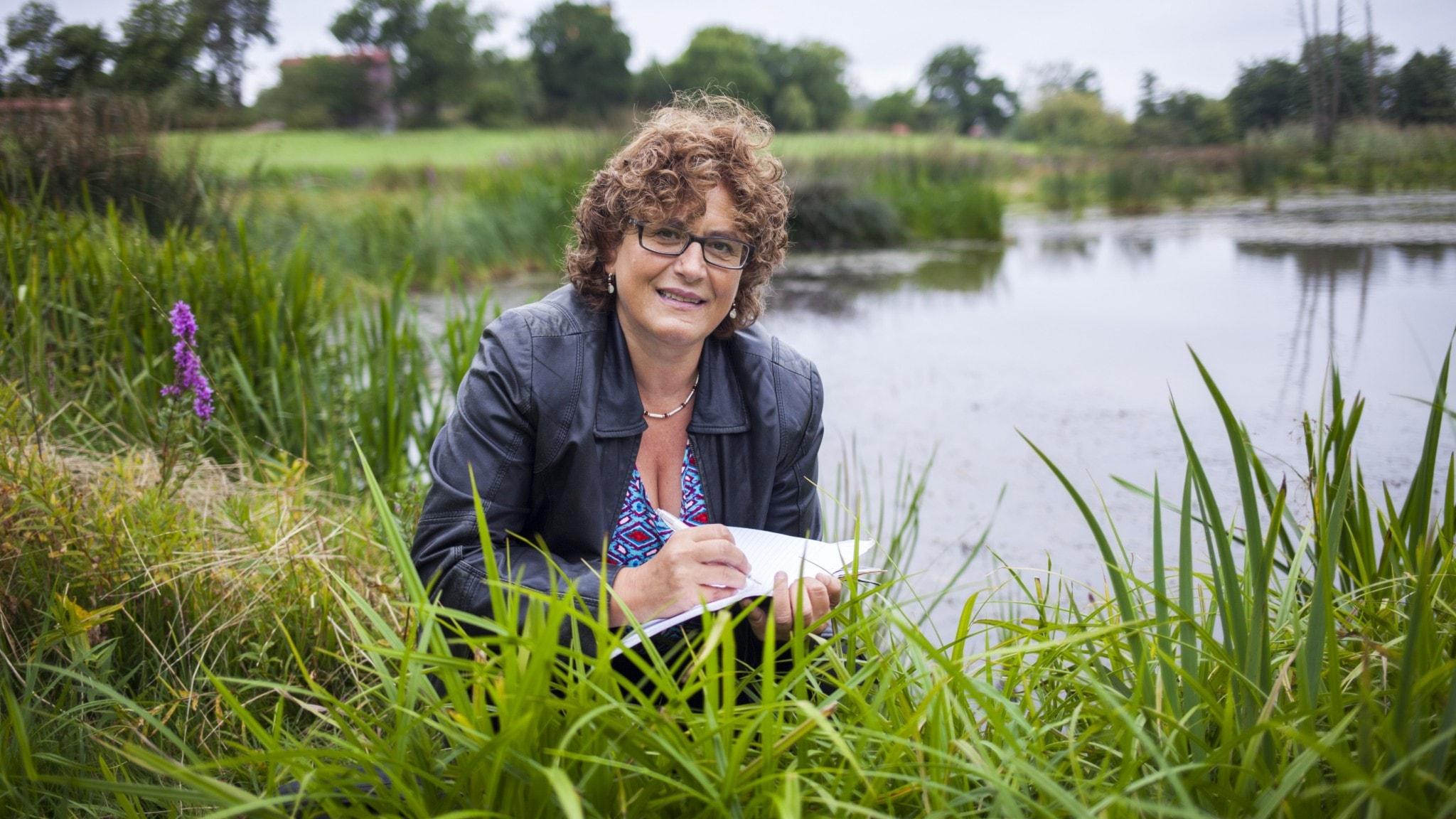 En kvinna med lockigt hår och glasögon hukar sig bland vass framför en sjö med ett block och penna i handen.