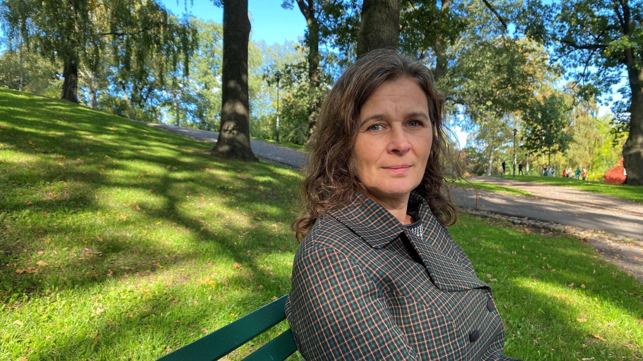 Åsa Svenfelt sitter på en bänk i en park.