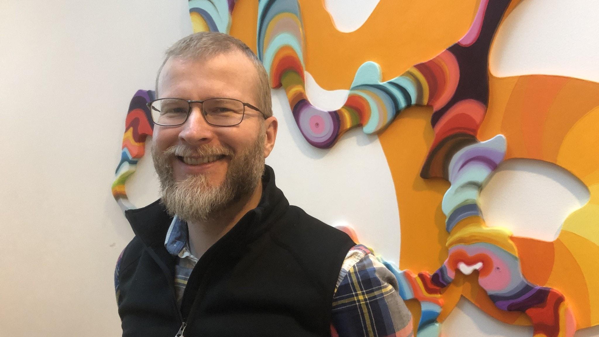 Marcus Nohlberg framför en färgglad väggdekoration