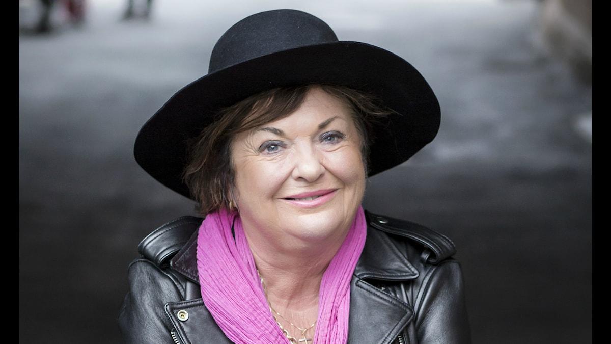 Viveca Lärn i rosa halsduk och svart hatt.