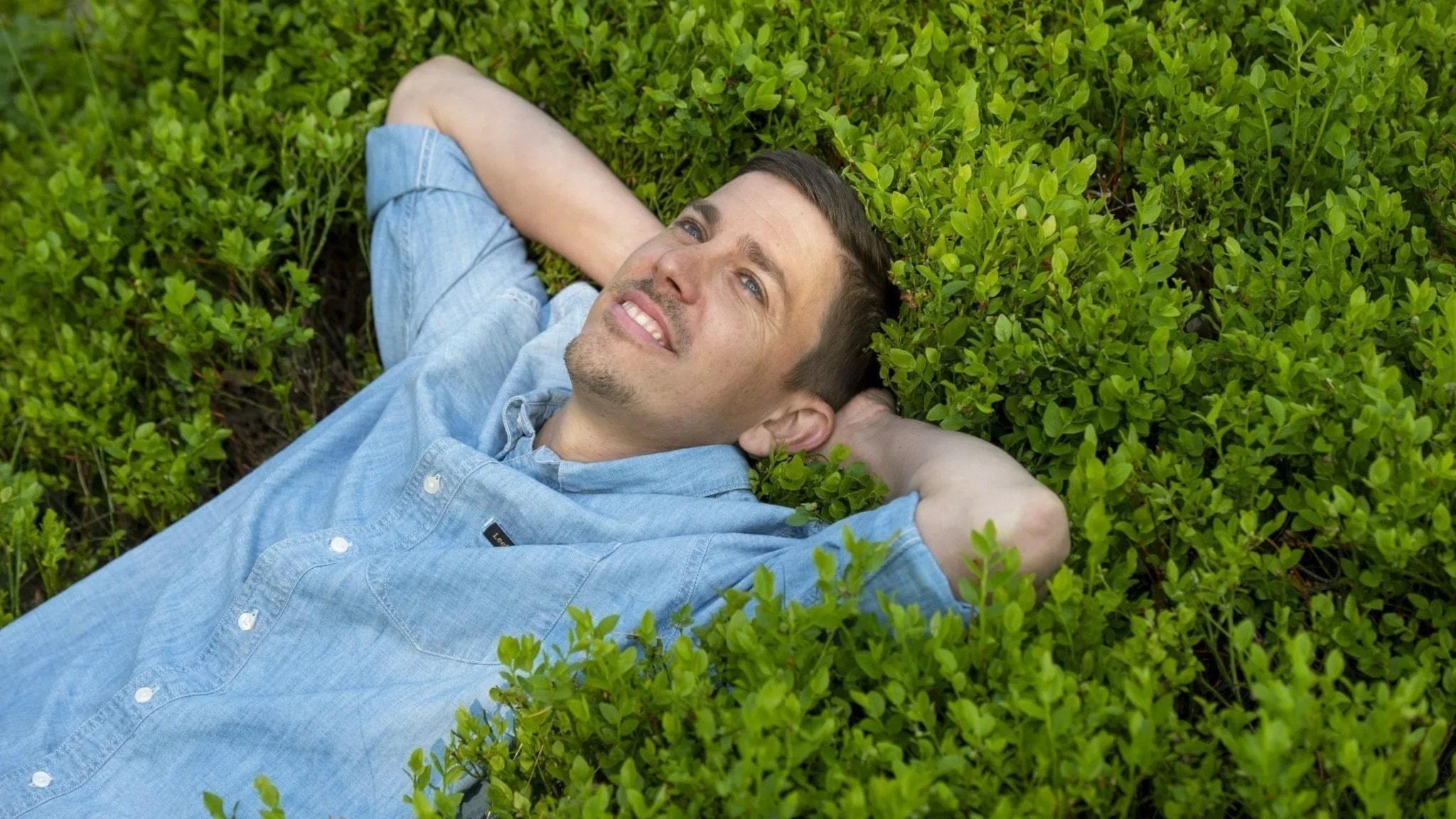 Programledaren Lars Svan ligger i gröngräset