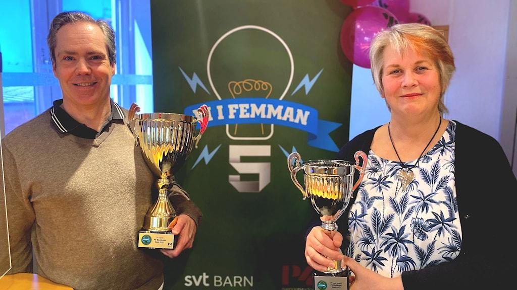 Domare Ola Palmgren och programledare Ingrid Elfstråhle står med var sin Vi i femman-pokal i famnen.