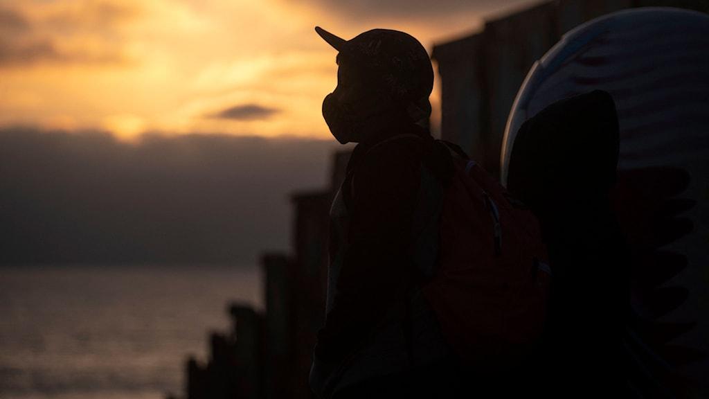 Ett barn till migranter i mexikanska staden Tijuana tittar mot gränsen mellan USA och Mexiko under en kvällsdemonstration mot våld mot migranter.