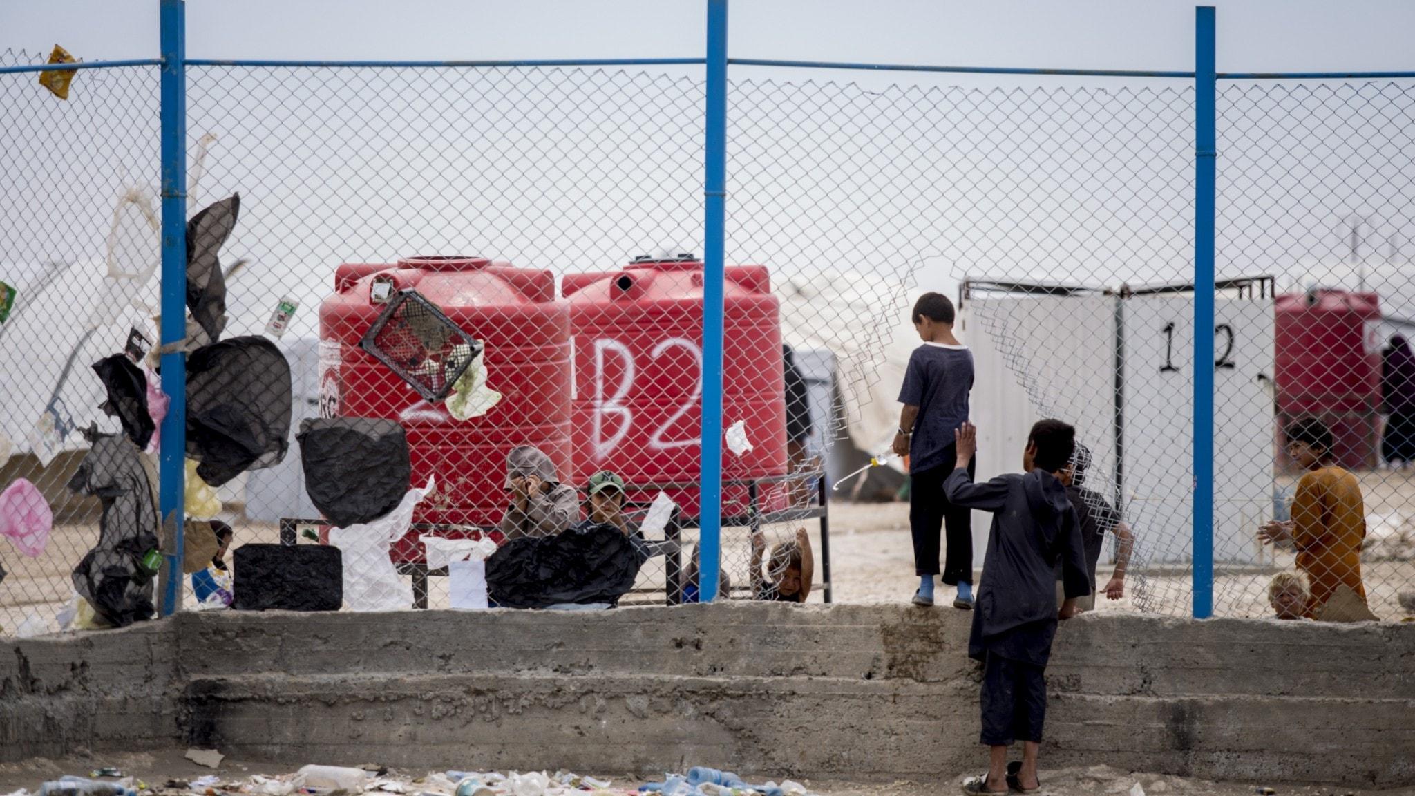 Barn står vid ett stängsel vid det ökända Al Hol-lägret i norra Syrien där kvinnor och barn som bott i IS kalifat nu hålls fångna.