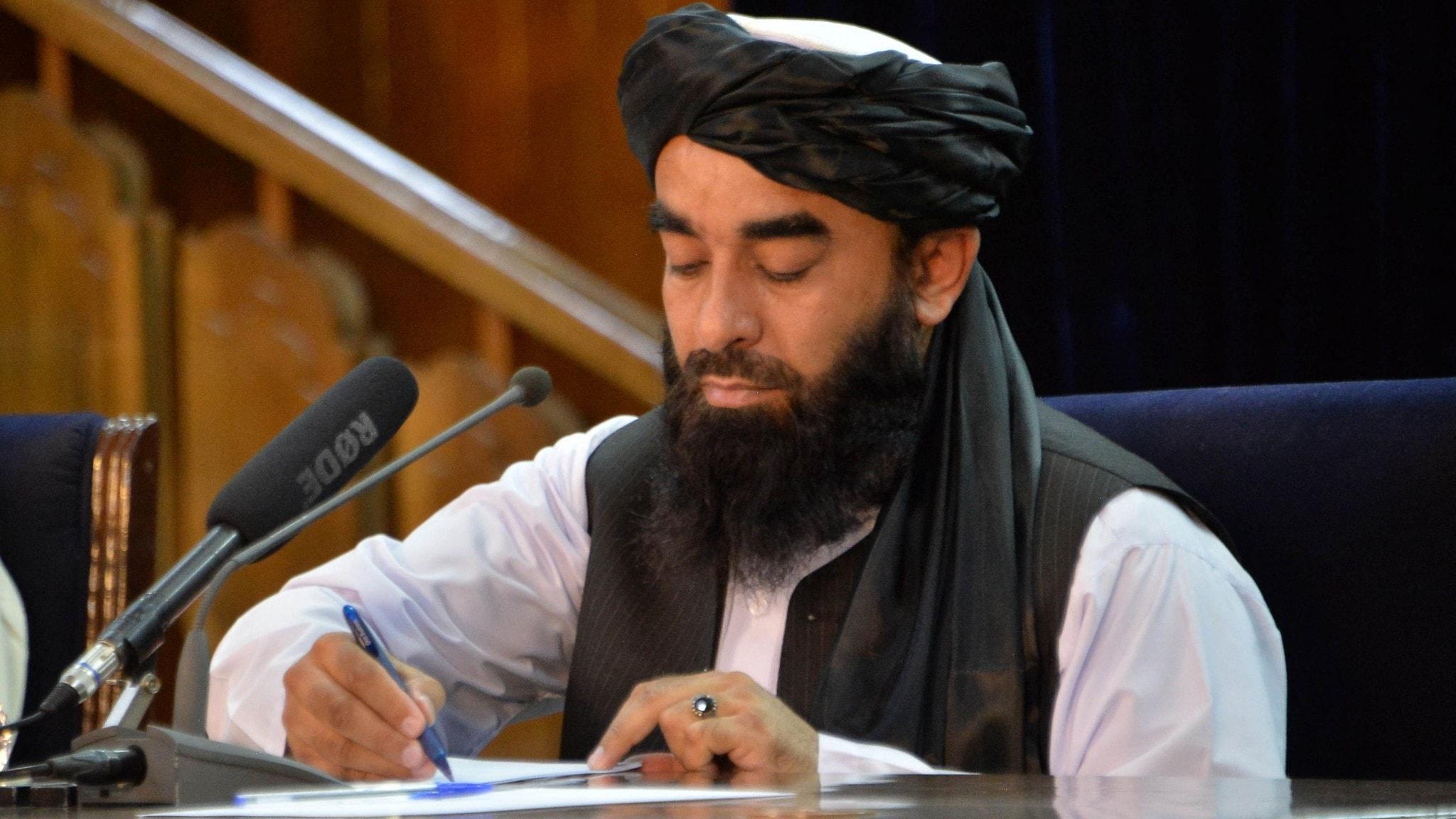 Talibanernas talesperson antecknar under en presskonferens i Kabul 24/8 strax efter att gruppen överraskande tagit makten i Afghanistan.