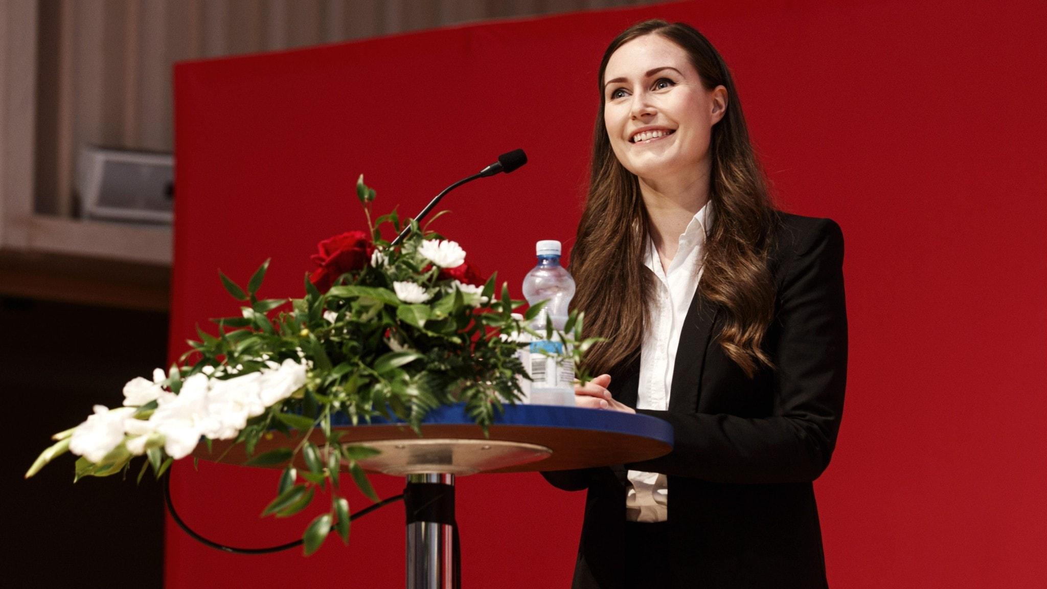 Finlands statsminister Sanna Marin vid ett podium med blommor.
