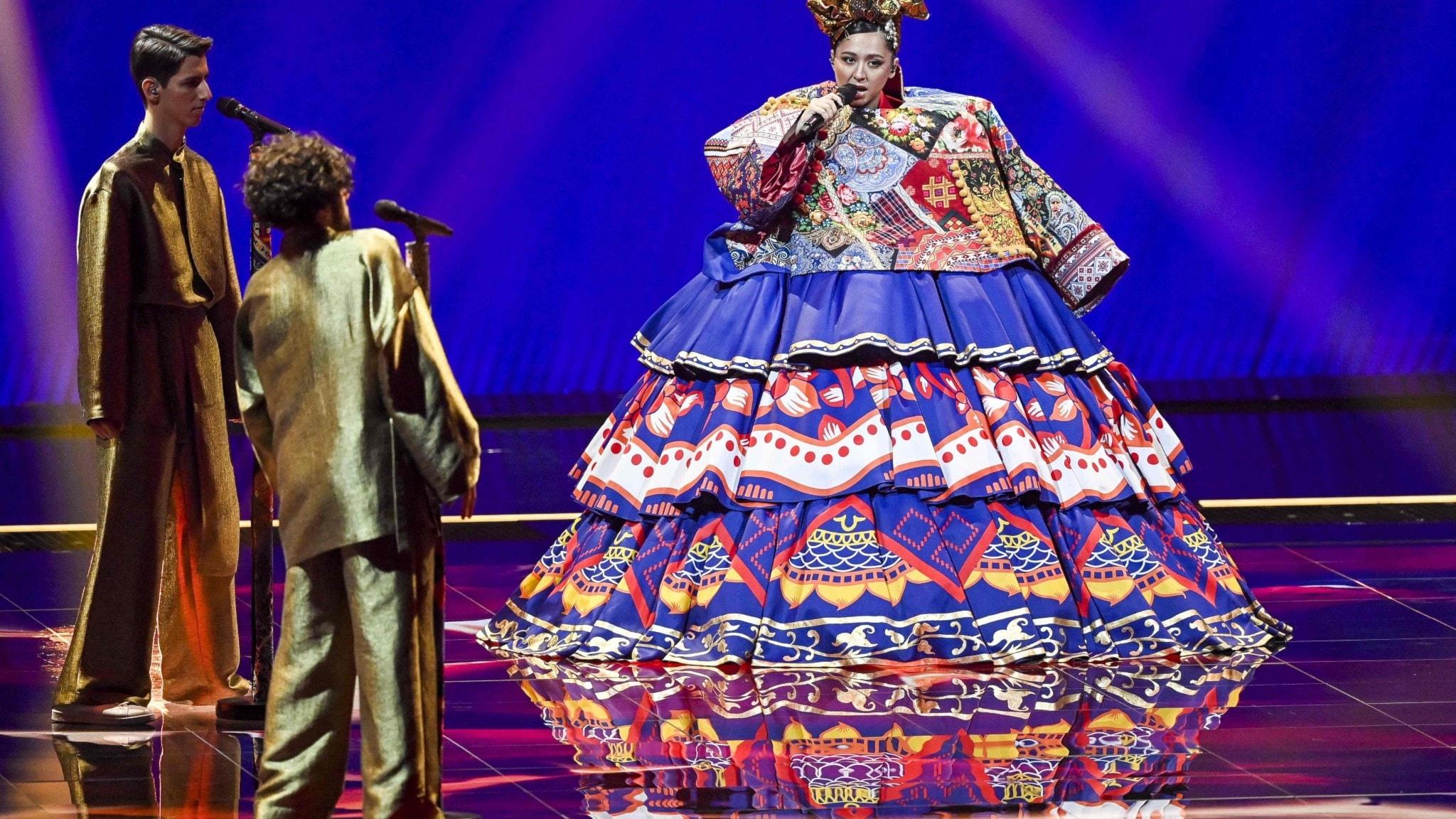 Den ryska artisten Marizha, som tävlar för sitt land i årets Eurovision Song Contest, står på scen i en stor folkloristisk klänning.