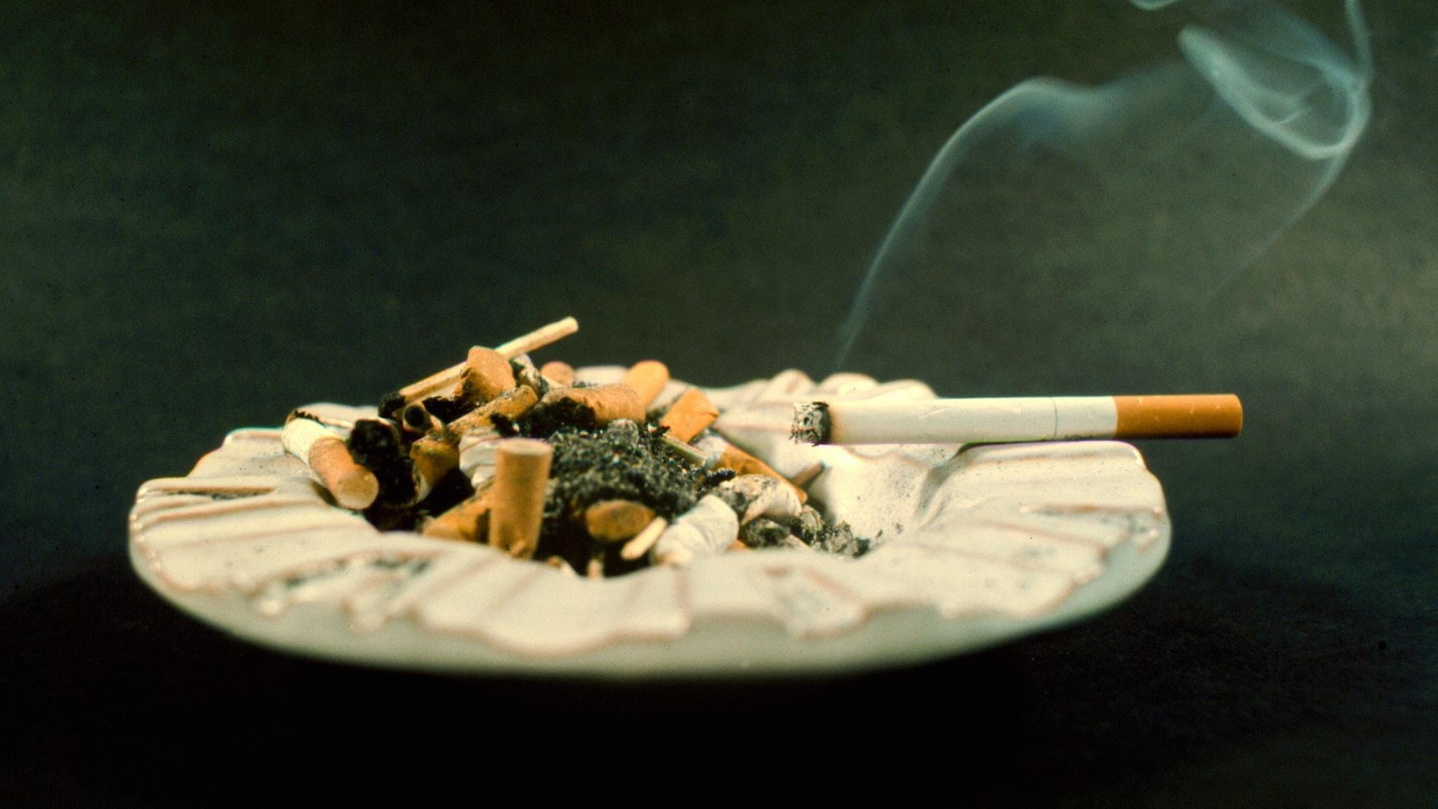 Bilden visar ett askfat med en rykande cigarett.