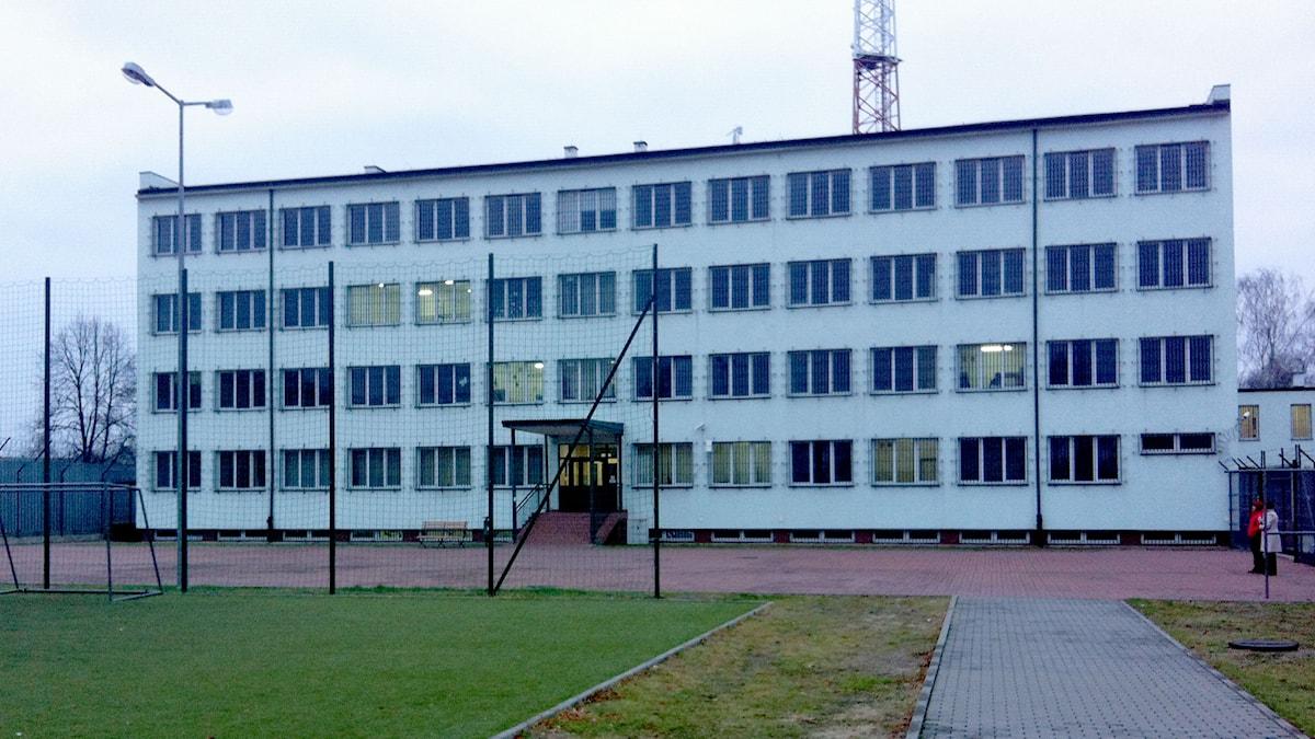 Ett avlångt fyravåningarshus bakom höga stängsel. Foto: Johanna Sjövall/Sveriges Radio.
