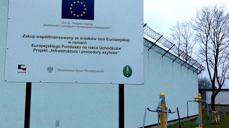En skylt med EU-symbolen vid en lekplats vid en mur med taggtråd. Foto: Johanna Sjövall/Sveriges Radio.