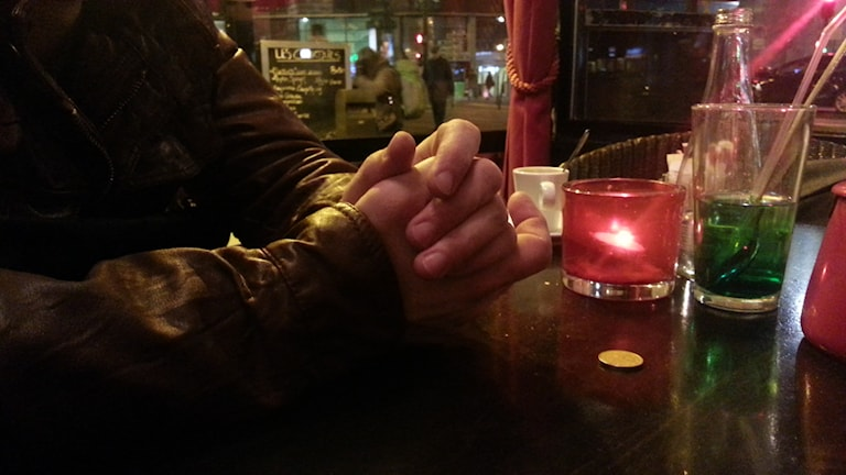 Man med knäppta händer vid ett cafébord. Foto: Radio France.