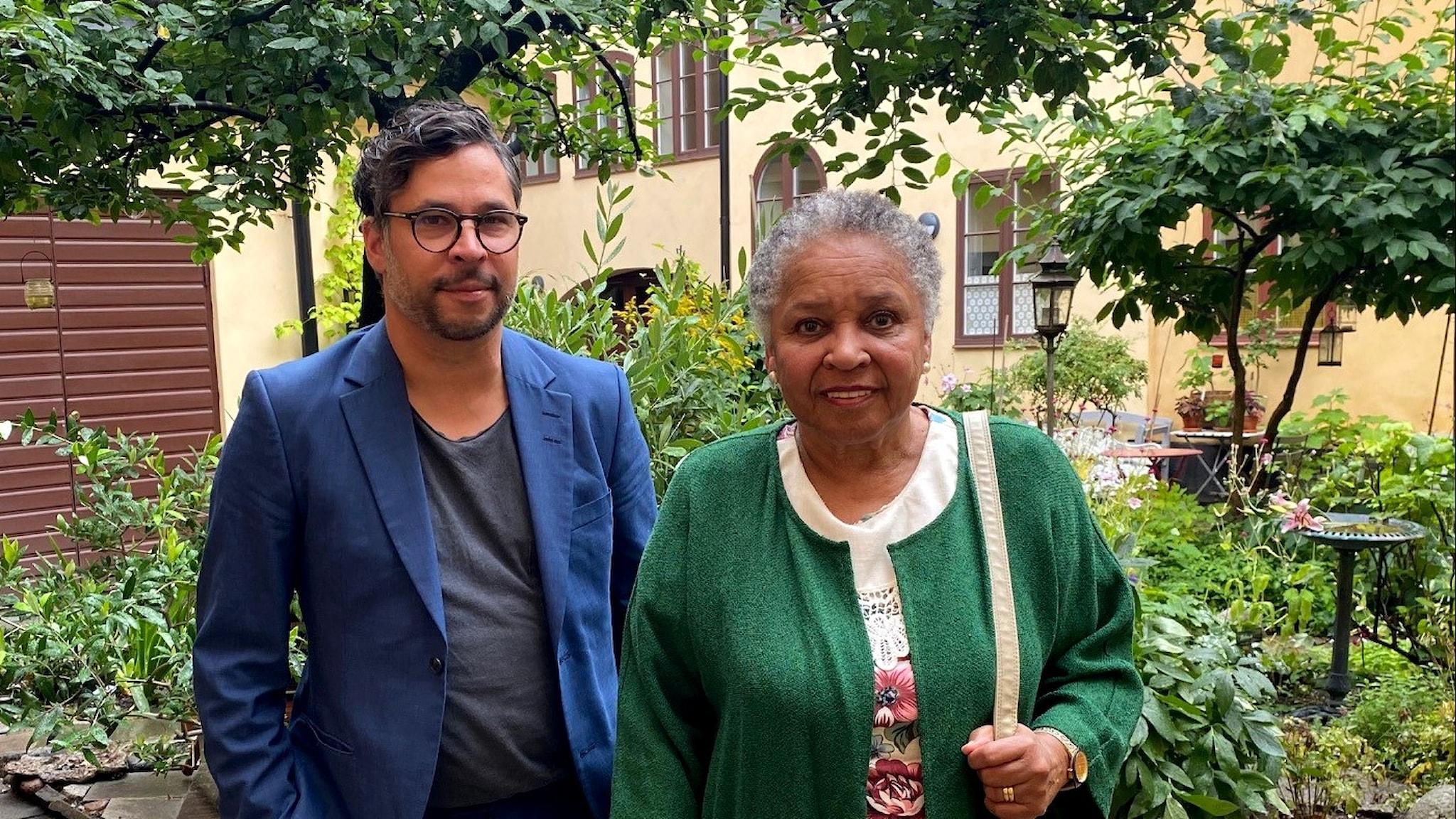 Martin Wicklin och Gloria Ray Karlmark står i en lummig trädgård