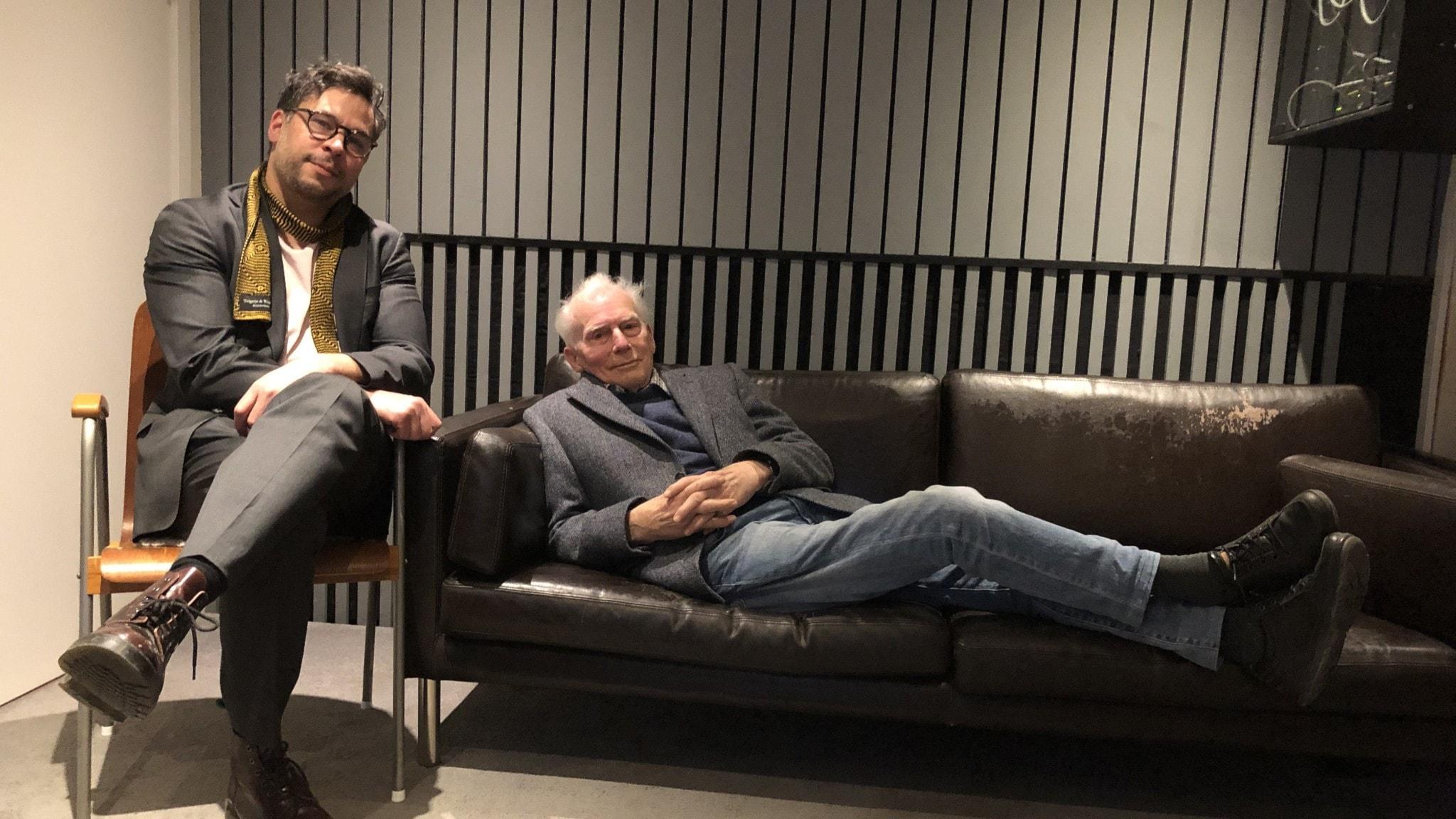 Martin Wicklin sitter på en stol och hans gäst Johan Cullberg ligger på soffan.