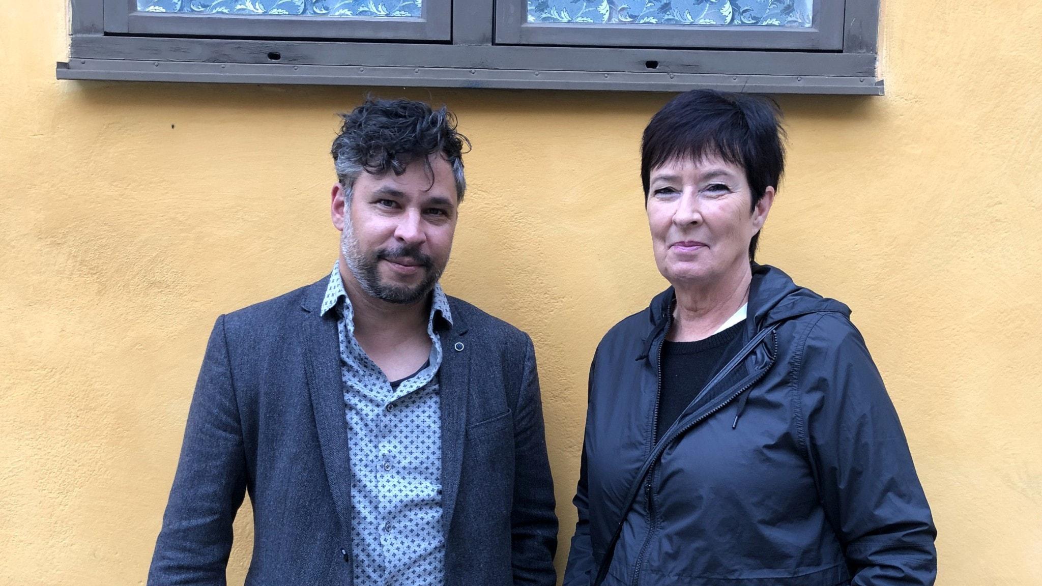 Mona Sahlin och Martin Wicklin står bredvid varandra mot en husvägg