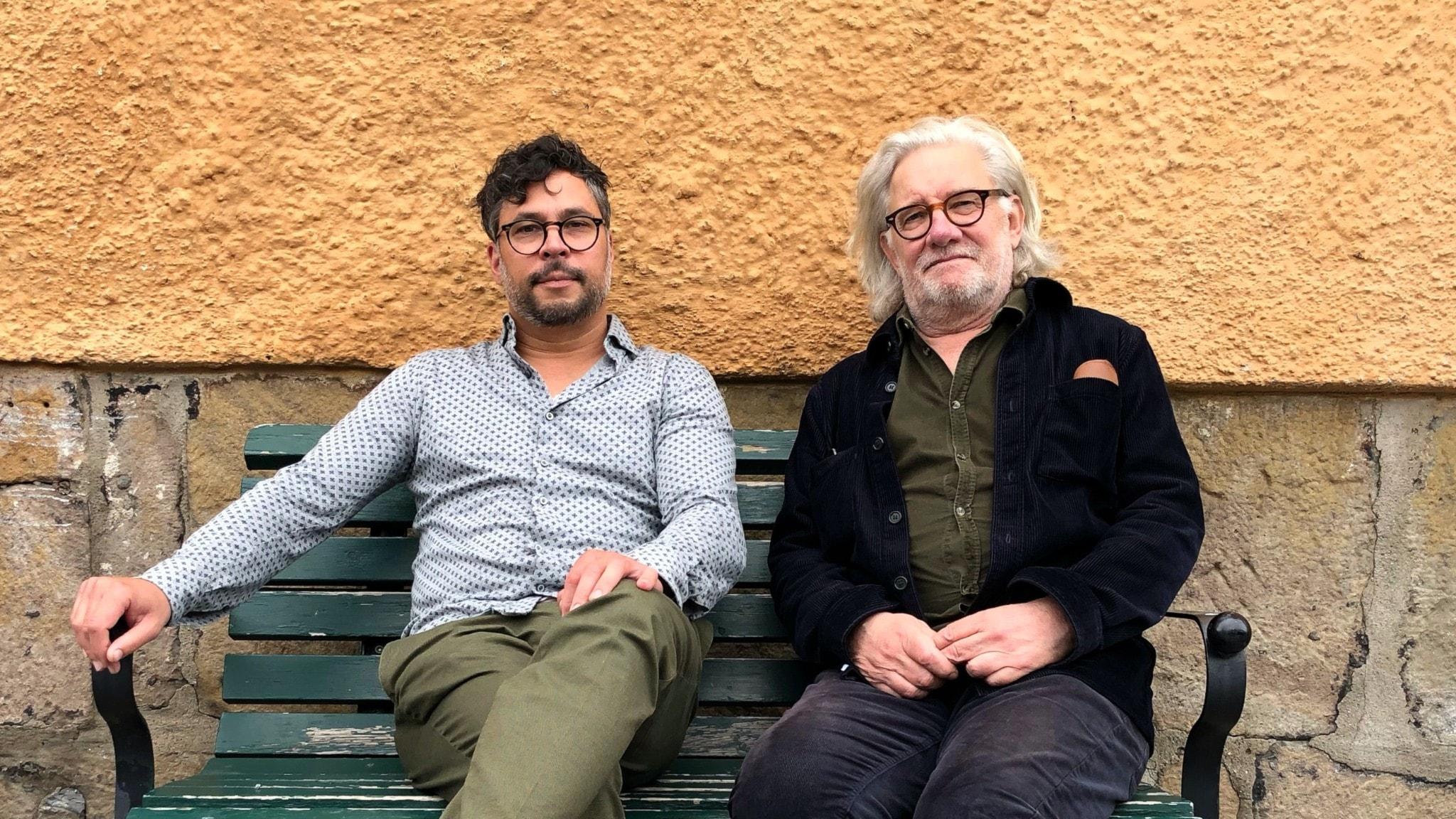 Martin Wicklin och Johan Croneman sitter bredvid varandra på en bänk.