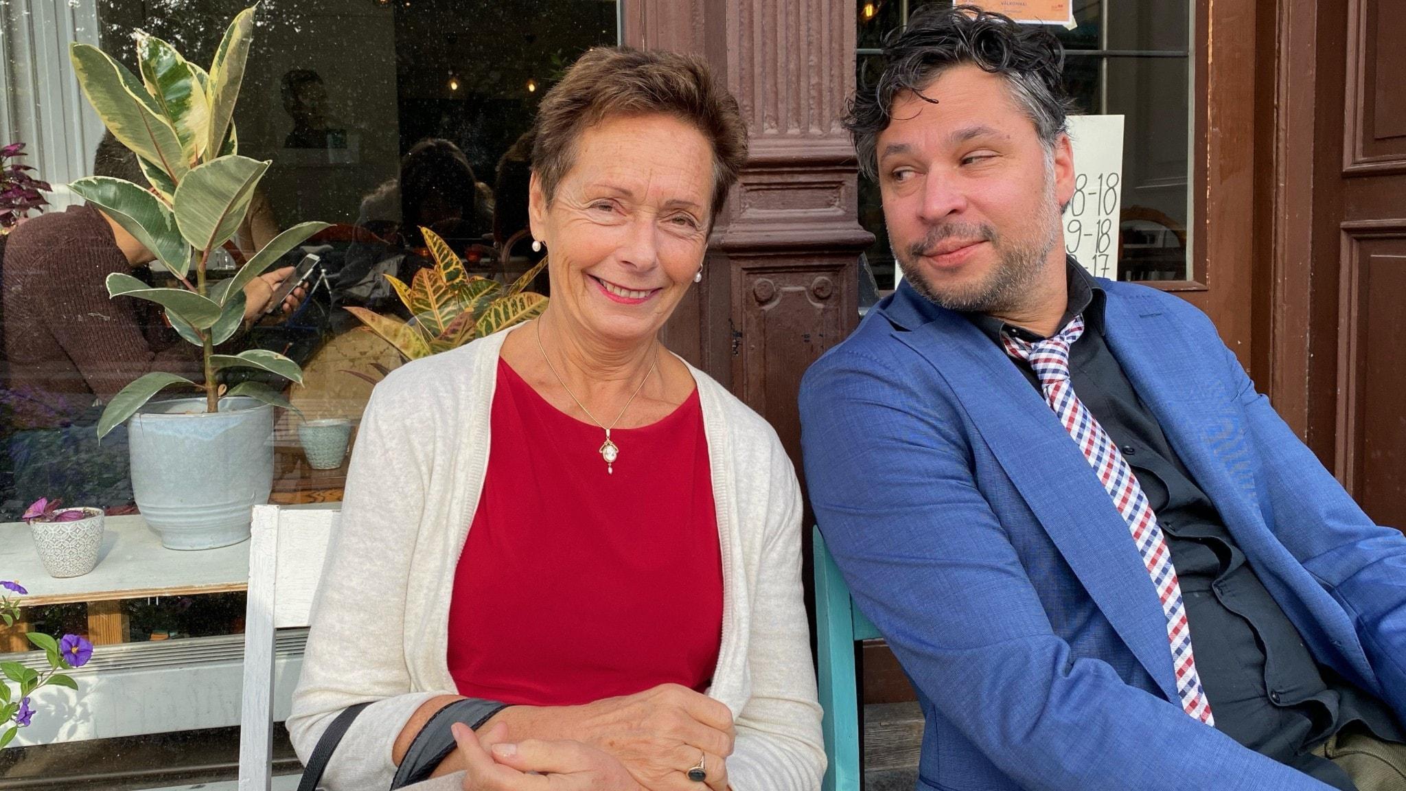 Dorotea Bromberg och Martin Wicklin sitter bredvid varandra utanför ett kafé