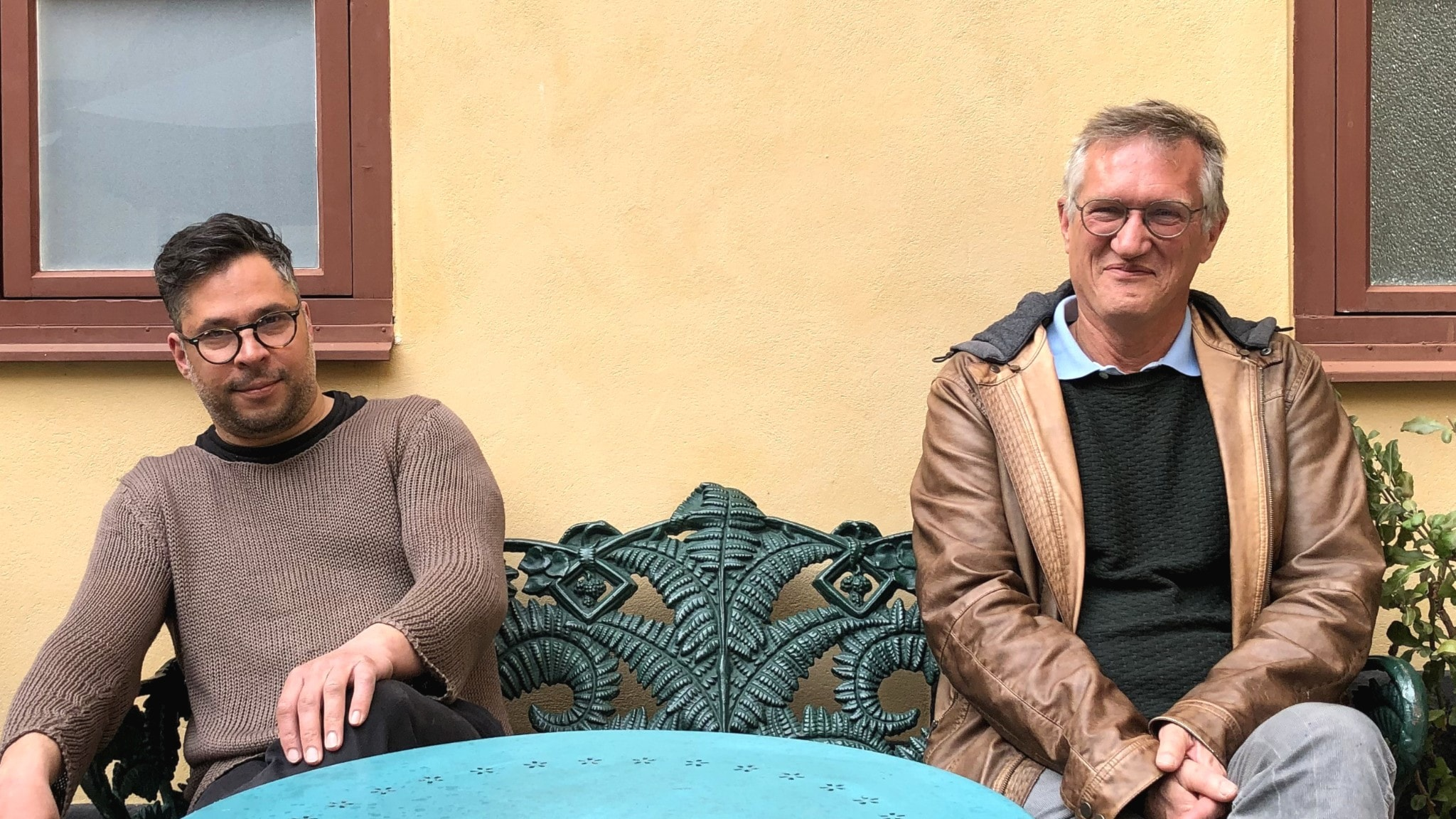 Anders Tegnell och Martin Wicklin sitter på en bänk bredvid varandra med avstånd