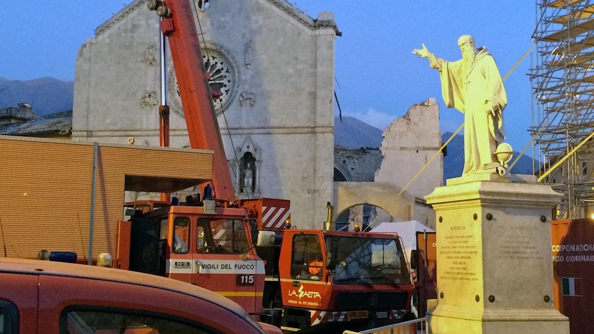 Statyn av Sankt Benedictus på torget i Norcia. Av Sankt Benediktus katedral står bara en vägg kvar.
