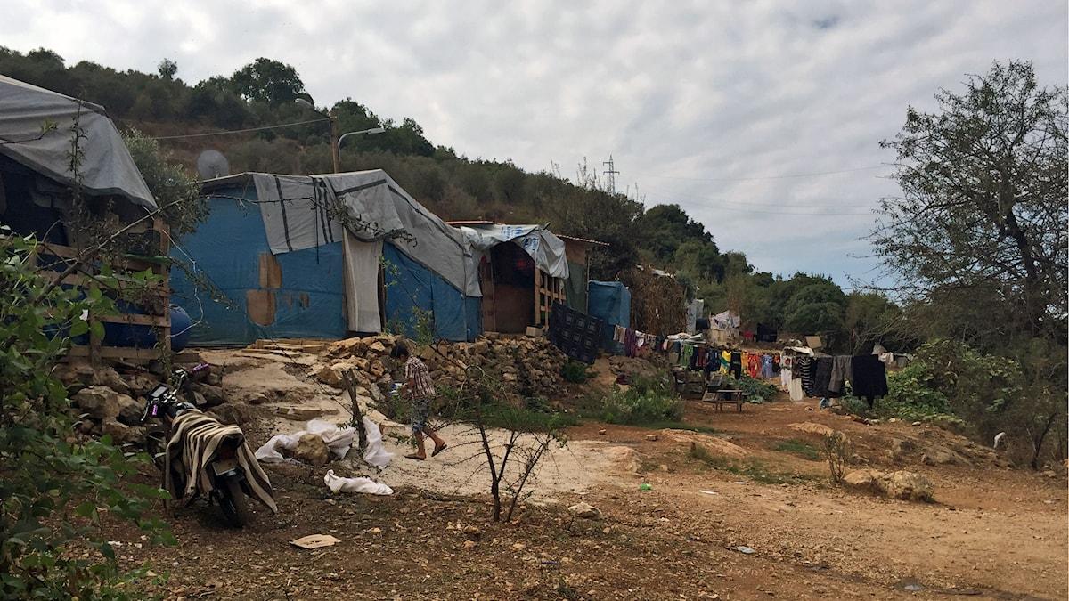 Enkla skjul byggda av plankor och presenningar. Kläder häger och torkar på linor. Ett flyktingbarn går mot skjulen.