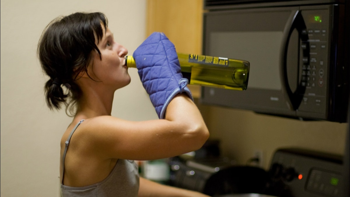 Kvinna dricker vin och lagar mat. Foto: Bucky Schwarz Flickr (CC BY-NC-SA 2.0)