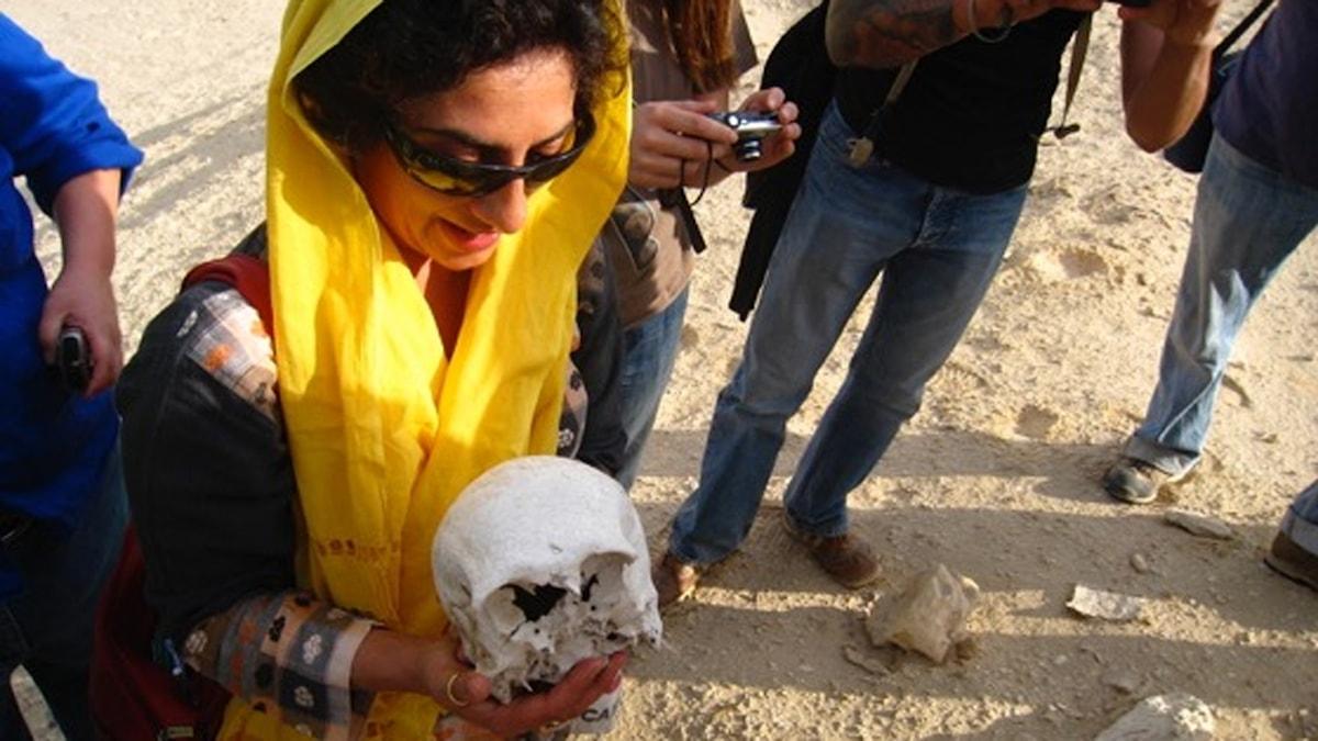 En kvinna står med en skelettdel.