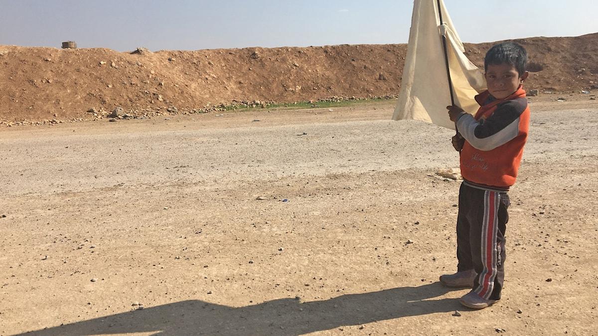 En pojke står med en vit flagga.