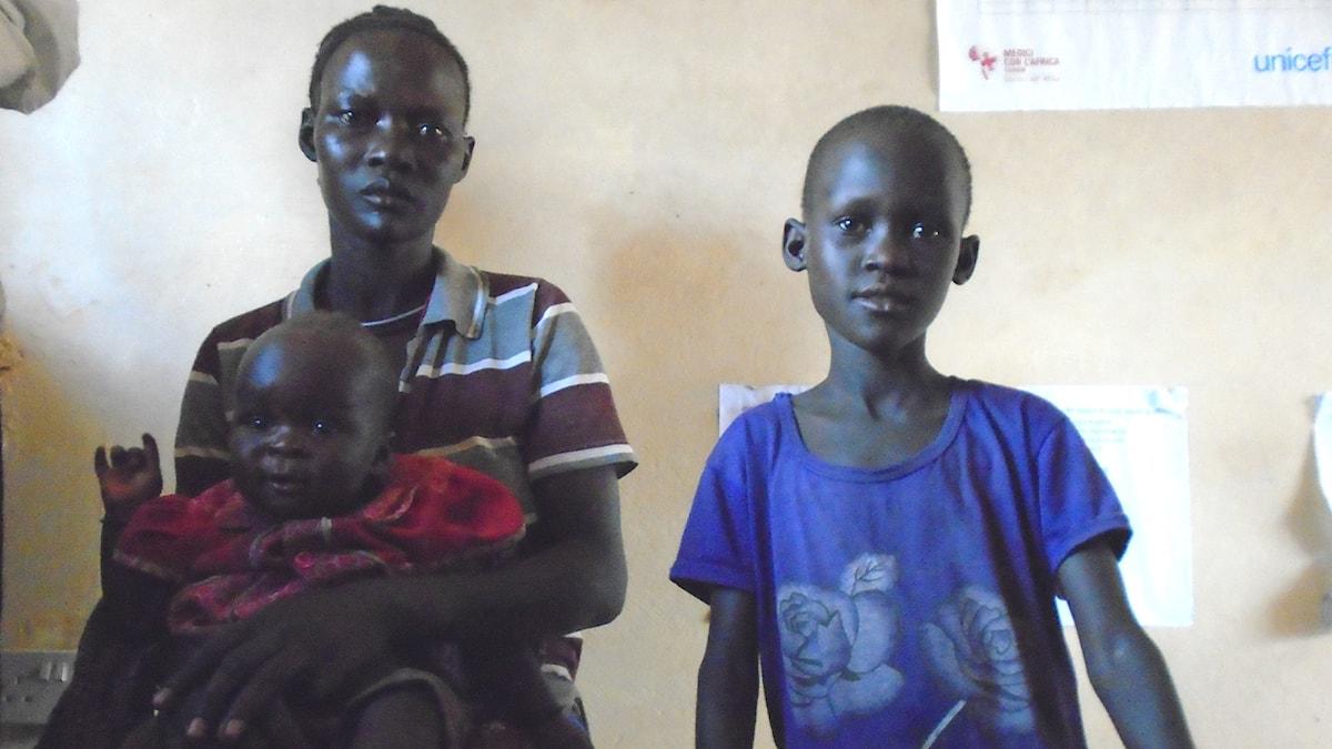 Alice Achuka i Karamoja Uganda med två av sina barn som blev matförgiftade (mer än 290 fall på sjukhus och minst tre döda), sannolikt av FNs matprograms grötpulver Super cereal. Foto: Edward Eninu / Sveriges Radio