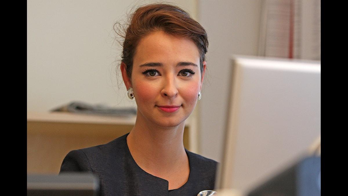 Bild på Alice Teodorescu, sitter bakom en dator.