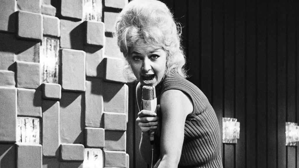 Anita Lindblom som sjunger i en mikrofon.