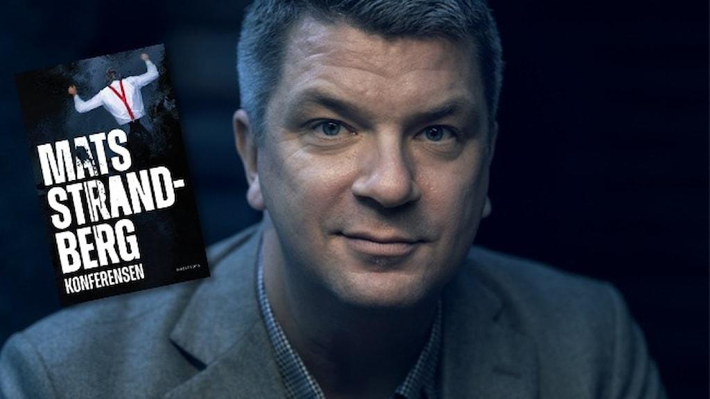 """Porträtt av författaren Mats Strandberg, klädd i blå kavaj. Infällt i bilden är omslaget till hans bok """"Konferensen""""."""