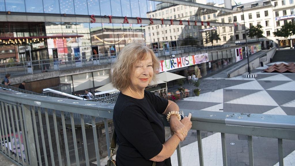 Författaren Lotta Fristorp står vid Sergeltorg med armarna lutade mot ett staket.