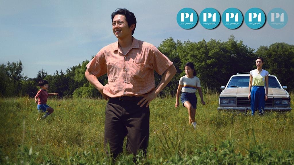 En man står i ett fält, klädd i rosa skjorta. Bakom honom syns tre personer och en bil.