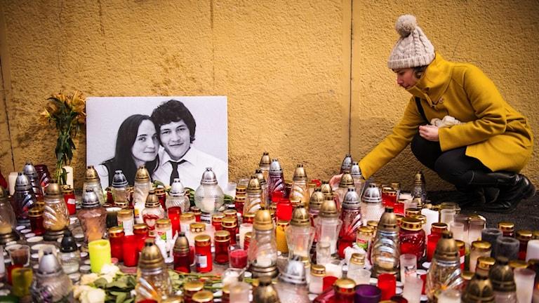 En kvinna tänder ett ljus vid en minnesplats för journalisten Jan Kuciak och hans flick
