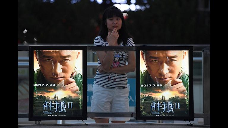 En ung kvinna bredvid två filmaffischer för Wolf Warriors 2