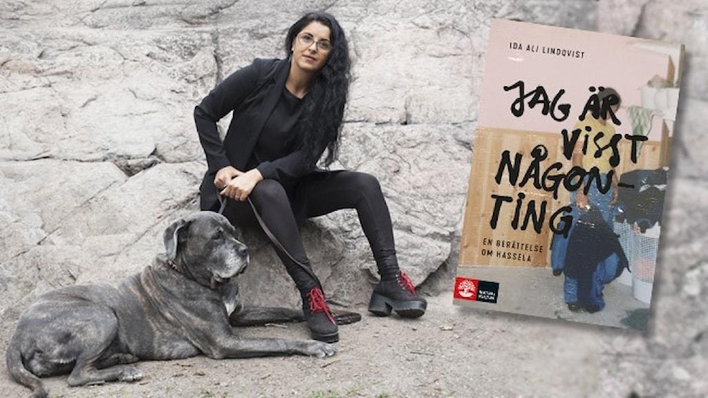 """Författaren Ida Ali-Lindqvist, helt klädd i svart, sitter på en klippa tillsammans med en stor, grå hund. Infällt är omslaget till hennes debutbok """"Jag är visst någonting""""."""