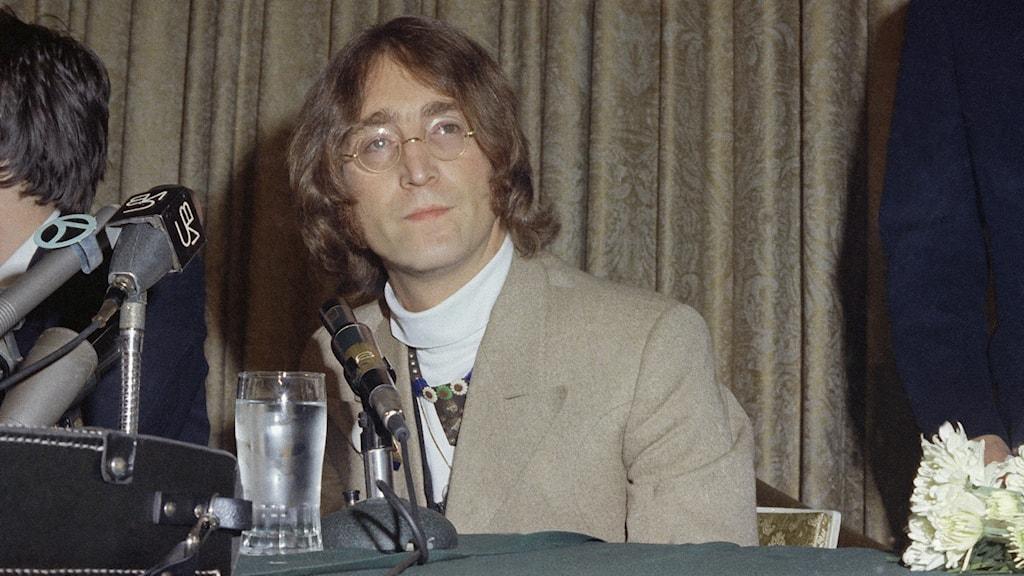 Johan Lennon klädd i vit polotröja och beige kavaj.