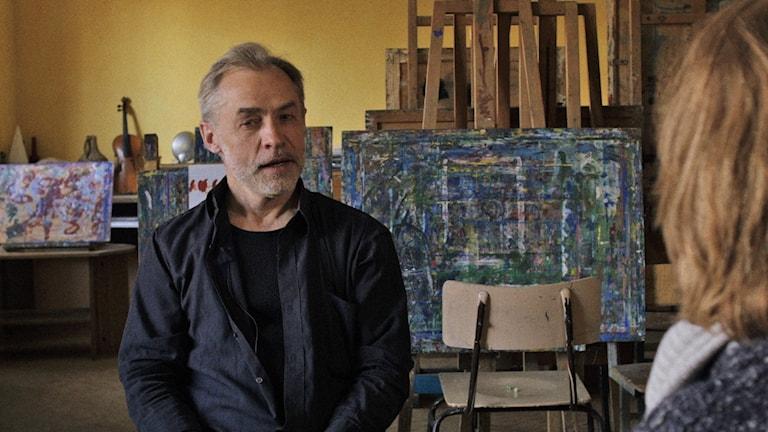 "Vladimir Sjtjelkun intervjuas i sin ateljé av Svetlana Aleksijevitj. Scen ur filmen ""Lyubov -kärlek på ryska"""