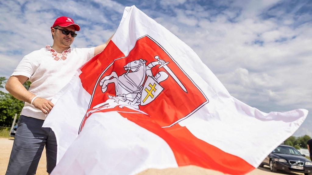 En person står med en röd och vit flagga.