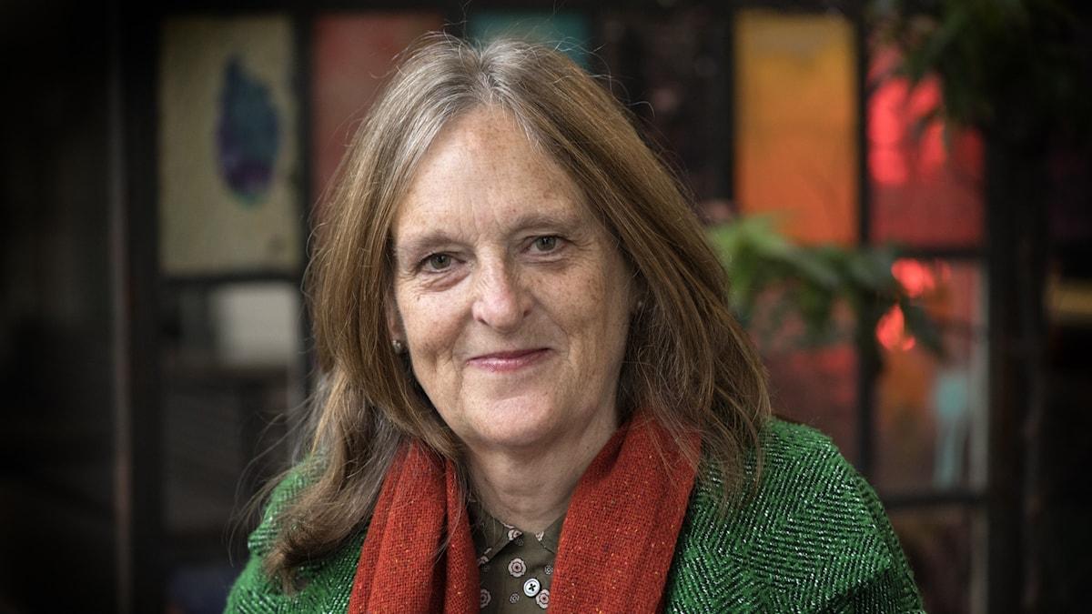 Ett porträtt av författaren Tessa Hadley klädd i grön kappa och roströd halsduk.