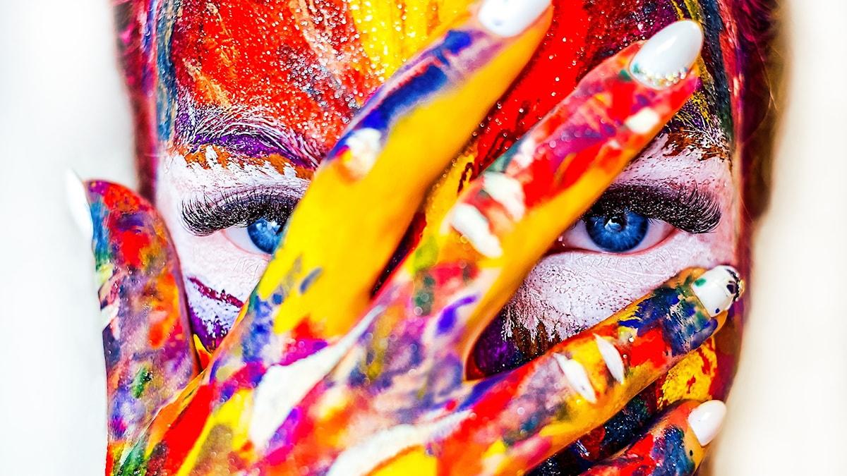 En kvinna täckt med färg håller för sitt ansikte.