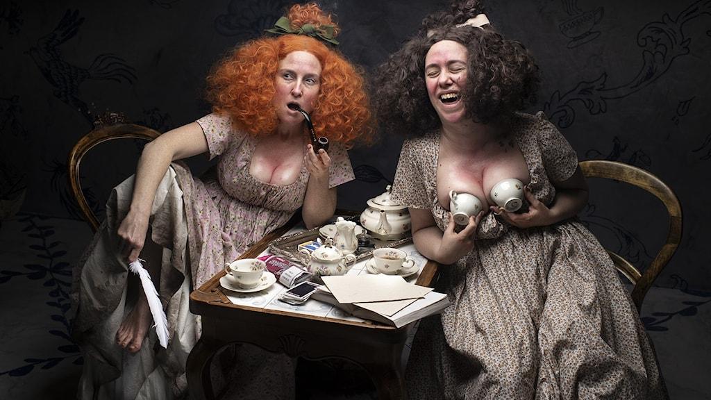 De två skådespelarna Lisen Rosell och Amanda Apetrea sitter vid ett bord med hoppar, klädda i gammaldags kläder med djupa urringningar. Bild från Turteaterns uppsättning av Stolthet och fördom.