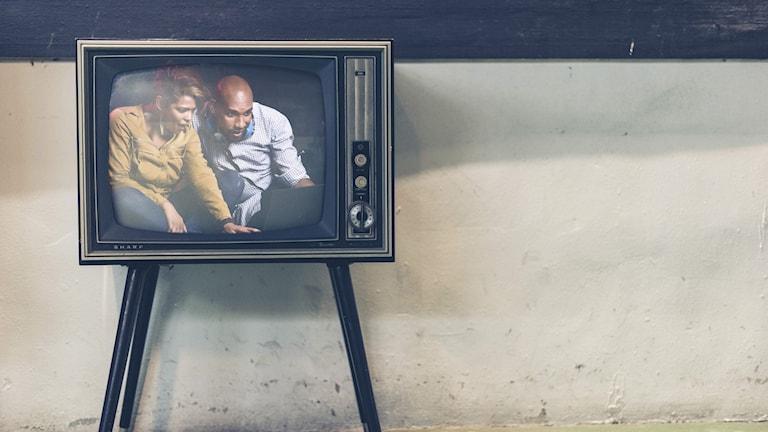 En tv med två personer som tittar på datorn.